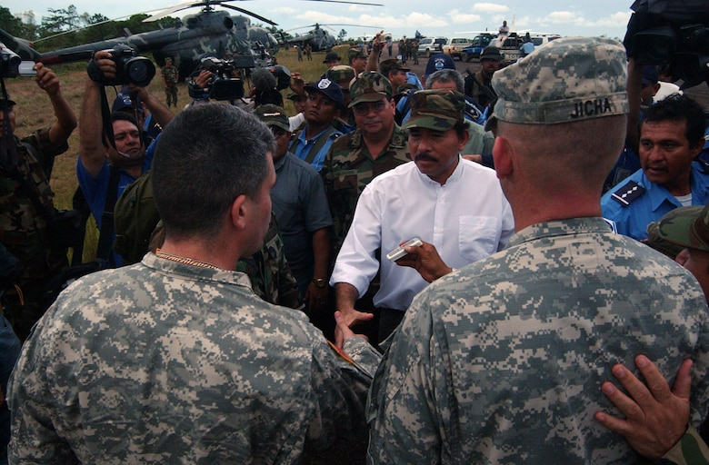 PUERTO CABEZAS, Nicaragua -- Army Capt. Jon-Paul Lavandeira (left) and Lt. Col. Gregory Jicha, both assigned to Joint Task Force-Bravo at Soto Cano Air Base, Honduras, greet Nicaraguan President Daniel Ortega among a media frenzy after arriving at a small airfield here Sept. 5.  The Army officers are part of a 13-person task force that deployed here to assess damage from the storm.  US Air Force photo by Tech. Sgt. Sonny Cohrs