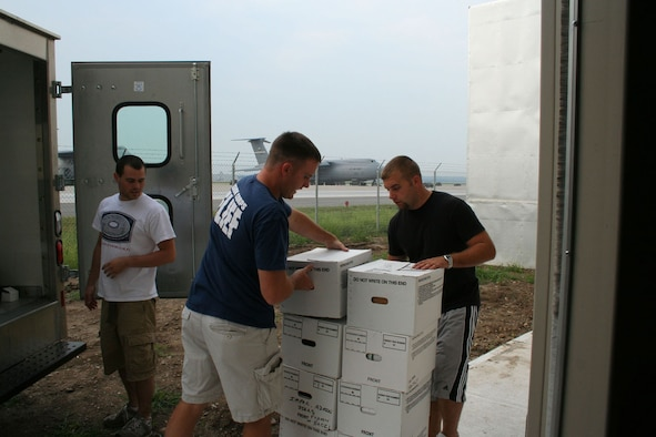 WRIGHT-PATTERSON AFB, Ohio - Reservists from the 89th Airlift Squadron, left to right, Bryant Fox, Matt Pfeifer, and Blake LeMaster unload boxes into the new C-5 Squadron Operations Facility Sept. 6, 2007. The new building will support squadron operations; this includes aircrew, life support, intelligence, training, and office space.  (U.S. Air Force photo/Mary Allen)