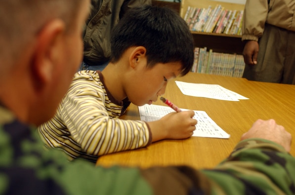 Gunsan City, South Korea -- A child searches for a word during his English class as Maj. Richard Fitzgerald, 8th Fighter Wing Chaplain, assists at the Gunsan Orphanage here Sept. 5.  The 8th Logistics Readiness Squadron volunteered at the Kunsan Air Base Commissary to raise money for the children at the Gunsan Orphanage as part of a Good Neighbor Program initiative. After presenting the money, they spent time with the children.  (U.S. Air Force photo/Senior Airman Steven R. Doty)