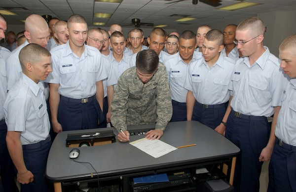 Leading by example, Brig. Gen. Darrell Jones, a former 37th Training Wing commander at Lackland Air Force Base, signs his Combined Federal Campaign form in front of some of the Air Force's upcoming Airmen currently assigned to Flights 559 and 560 of the 326th Training Squadron on Sept. 4, 2007. (USAF photo by Alan Boedeker)