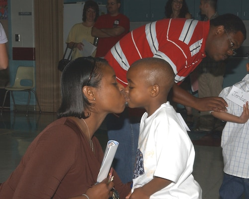 Staff Sgt. Lashana Rivers gives her 4-year-old, Deandre, a goodbye kiss before sending him off to his first day of school Aug. 27, 2007, at the Lackland Elementary School. Sergeant Rivers is assigned to the 59th Diagnostics and Therapeutics Squadron. (USAF photo by Alan Boedeker)