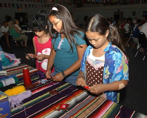 From left, Alexia Buentello, 9, Rachel Martinez, 12, and Meryl Belisario, 10, make Ojos de dios, or God's eyes, at the crafts at the the booth sponsored by the Youth Group. Alexia is the daughter of Anna Buentello, 59th Labratory Squadron. Rachel is the daughter of Staff Sgt. Dutchess Martinez, 59th Training Squadron. Meryl is  the daughter of Master Sgt. Joel Belisario, 346 Training Squadron. The girls were attending the first International Folk Festival at Lackland AFB, Texas. (USAF photo by Alan Boedeker)