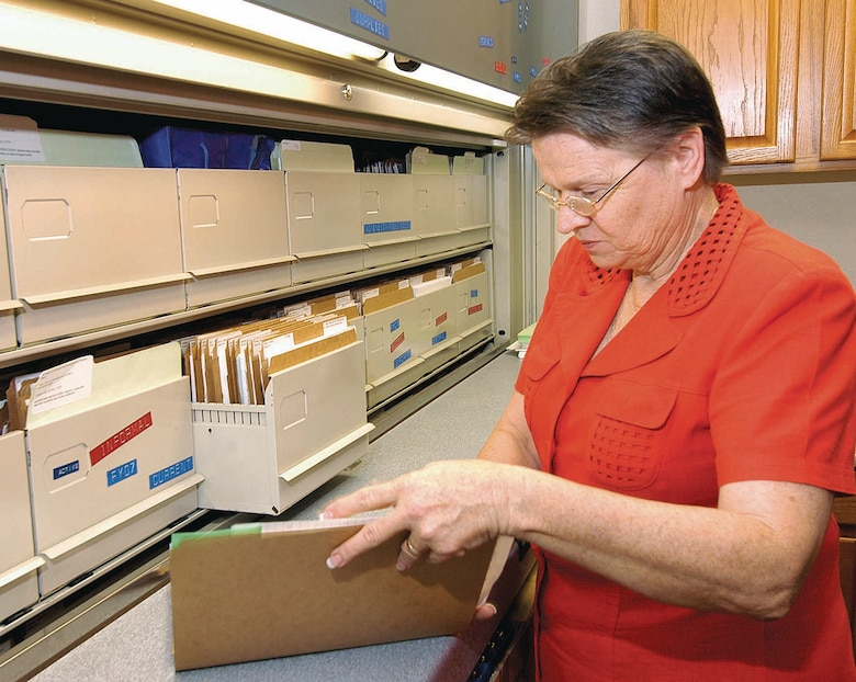 Carol Pope, an equal employment administrative assistant, manages a massive file system for ongoing and closed cases.  One case may yield files five inches thick with documents. (Air Force photo by Margo Wright)