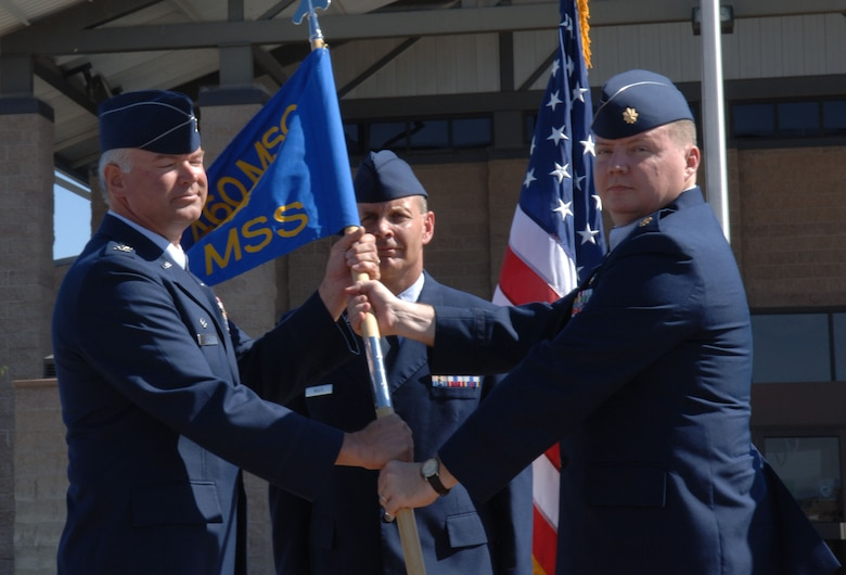 Col. Bart Hedley, 460th Mission Support Group commander, hands command of the 460th Mission Support Squadron to Maj. Thomas Smith during a ceremony Sept. 5. Major Smith assumed command from Lt. Col. Craig DeZern. Colonel DeZern is staying at Buckley to become the 460th Space Wing's director of staff. (U.S. Air Force photo by Airman 1st Class Chris Bush)