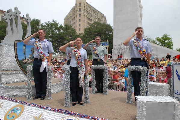 First Lt. Jennifer Ferrer (left center) joins other military ambassadors in saluting the official party from a float at the 2007 Fiesta celebration in downtown San Antonio. (U.S. Air Force photo by Rich McFadden)