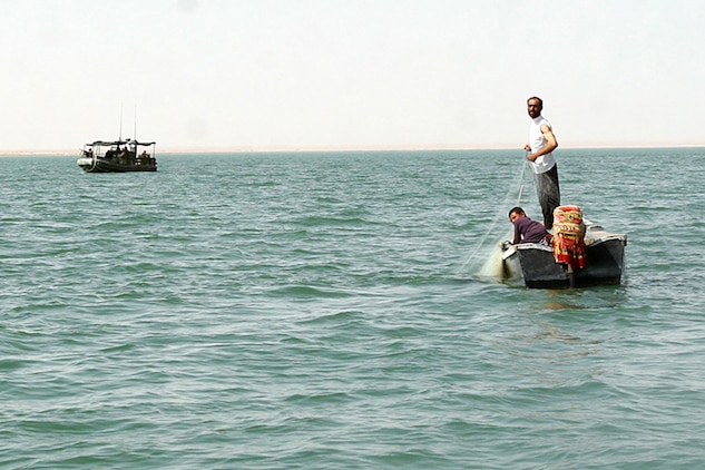 HADITHA DAM, Iraq, (Sept. 16, 2007) – Iraqi fisherman pull in their nets after being warned by sailors with Riverine Squadron 1, Riverine Group 1, Navy Expeditionary Combat Command, in support of Regimental Combat Team 2, about the new temporary 24-hour curfew on the Euphrates River near the dam. The regiment declared the temporary curfew on the waterway to stem the suspected increase of enemy activity on the river during the Muslim holiday of Ramadan. Official Marine Corps Photo By Cpl. Ryan C. Heiser.