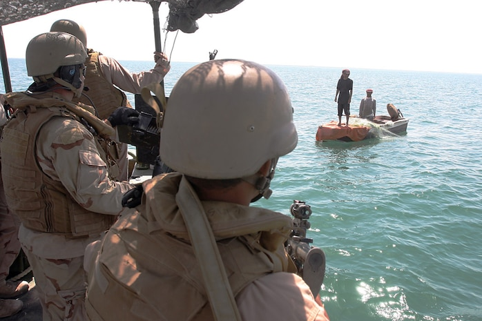 HADITHA DAM, Iraq, (Sept. 16, 2007) – Navy Petty Officer 2nd Class Lance C. Zielinski (left), a gunners mate with the Maritime Interdiction Operations Team, Detachment 3, Riverine Squadron 1, Riverine Group 1, Navy Expeditionary Combat Command, in support of Regimental Combat Team 2, and an interpreter (center) warn local fishermen of the new 24-hour curfew on the Euphrates River near the dam. The regiment declared the temporary 24-hour curfew on the waterway to stem the suspected increase of enemy activity on the river during the Muslim holiday of Ramadan. Official Marine Corps Photo By Cpl. Ryan C. Heiser.