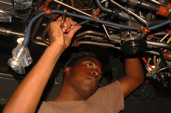 Airman 1st Class Christopher Mason installs a rear fuel drain bracket on an F-15C  F100-PW-220E jet engine at Kadena Air Base Sept. 11, 2007.  Airman Mason works in the aerospace propulsion flight in the 18th Component Maintenance Squadron.  (U.S. Air Force photo/Airman 1st Class Ryan Ivacic)