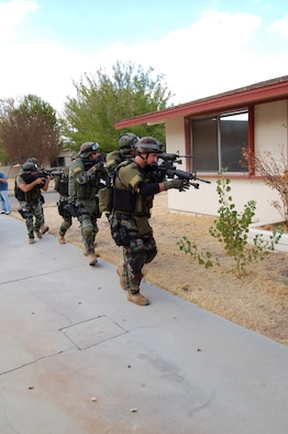 Kern County Sheriff's Department's Specialized Weapons and Tactics team, otherwise known as SWAT, prepares to enter a house during their training here Aug. 30. The base opened a vacant section of the Mesquite Meadows housing area for the SWAT team's training. (Photo by Airman 1st Class Julius Delos Reyes)