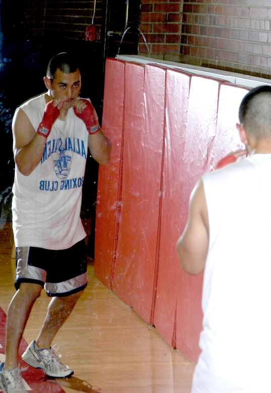 """Airman Buenting """"shadow boxes"""" in the mirror before he gets into the ring to spar with another member of the Warren boxing team. Boxers use mirrors to check their form while they are in their fighting stance."""