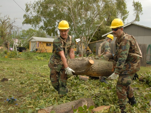 Senior Airman Brandon W. Miller, left, and Tech. Sgt. Richard M. Hayes, both of the 119th Wing, remove fallen tree branches and debris from yards in order to clear a path for power line workers in Northwood, N.D. Aug. 28.  The fallen trees are a result of an F4 category tornado that hit Northwood, N.D., in the early evening hours of Sunday, Aug. 26. (USAF photo/Senior Master Sgt. David H. Lipp)