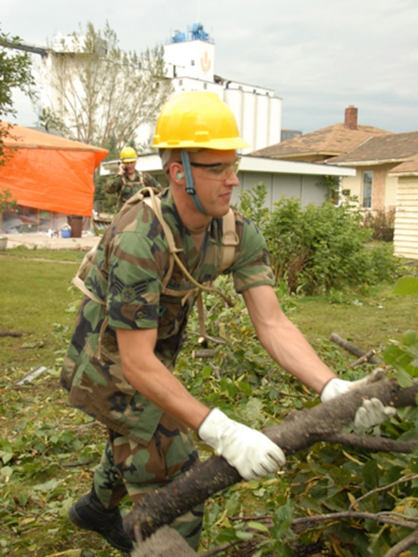 Senior Airman Brandon W. Miller, 119th Wing, removes fallen tree branches and debris from yards in order to clear a path for power line workers, Aug. 28, in Northwood, N.D.  The fallen trees are a result of an F4 category tornado that hit Northwood, N.D., in the early evening hours of Sunday, Aug. 26. (USAF photo/Senior Master Sgt. David H. Lipp)