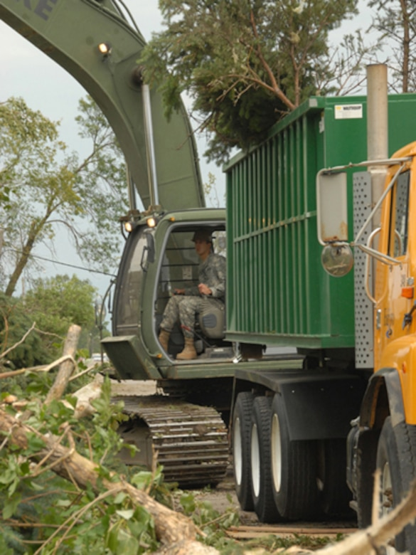 Sergeant Jay E. Haaland, 835th Engineer Team (Asphalt), clears large trees and branches and loads them into a dump truck using a hydraulic excavator in Northwood, N.D., Aug. 28.  The fallen trees are a result of an F4 category tornado that hit Northwood, N.D., in the early evening hours of Sunday, Aug. 26. (USAF photo/Senior Master Sgt. David H. Lipp)