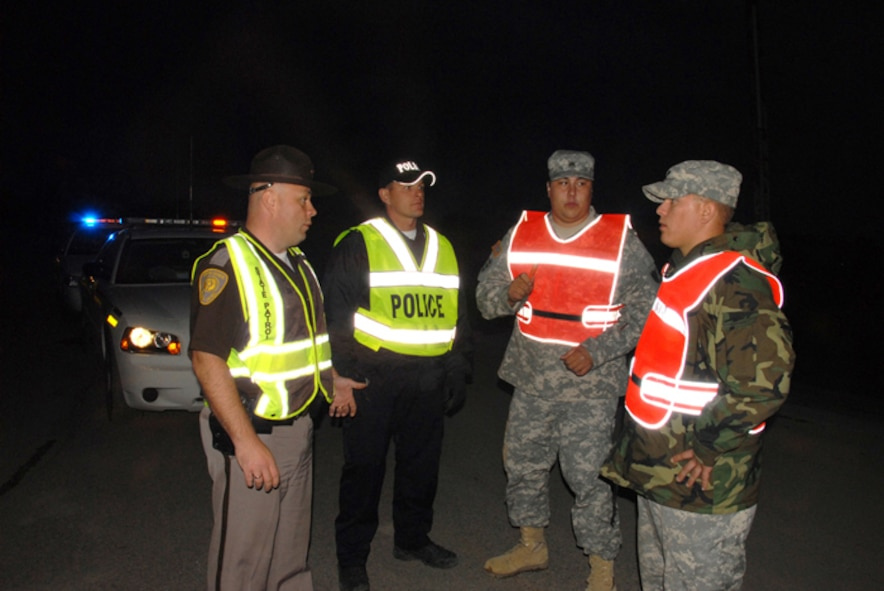 From right to left, Specialist Shane A. Korynta and Sergeant Danny J. Lemieux Jr., both of the 188th Engineer Company, assume security responsibilities at an entry control post on the outskirts of Northwood, N.D., from law enforcement officials Jeremy Hanson, Larimore, N.D., police chief, and N.D. Highway Patrol trooper Aaron Enzminger.  Entry to the town of Northwood was completely closed and secured by the North Dakota National Guard from 8 p.m. until 8 a.m. during the nights following an F4 tornado that hit Northwood, N.D., Sunday, Aug. 26. (USAF photo/Senior Master Sgt. David H. Lipp)