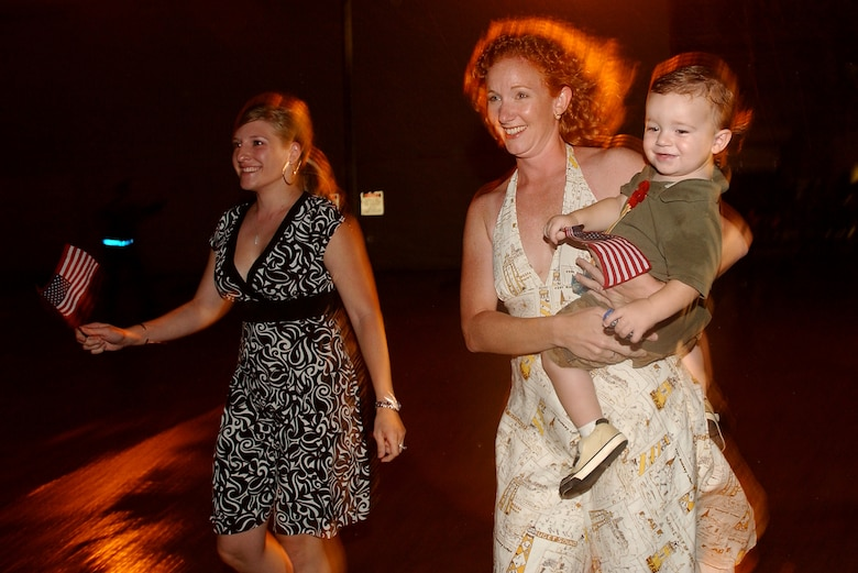 """A couple of wives run to their husbands after they landed  at Kadena AB, Japan, Sept. 10, 2007. The 31st Rescue Squadron held a """"Welcome Home"""" party after being deployed for four months. (U.S. Air Force photo/Tech. Sgt. Rey Ramon)"""