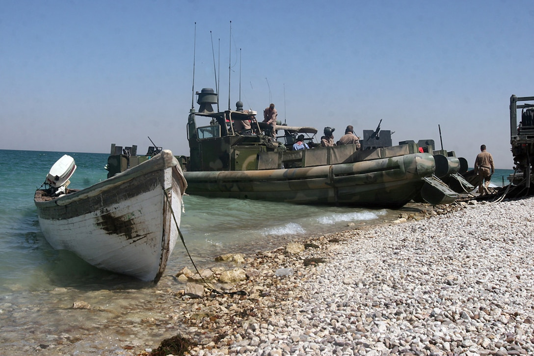 HADITHA DAM, Iraq, (Sept. 16, 2007) – An Iraqi civilian's boat sits on the shore of the dam as sailors with Riverine Squadron 1, Riverine Group 1, Navy Expeditionary Combat Command, in support of Regimental Combat Team 2, prepare to leave on a patrol to enforce the temporary 24-hour curfew on the waterway. The riverines warned locals of the new curfew for several days before seizing the boats of repeat curfew offenders. Official Marine Corps Photo By Cpl. Ryan C. Heiser.