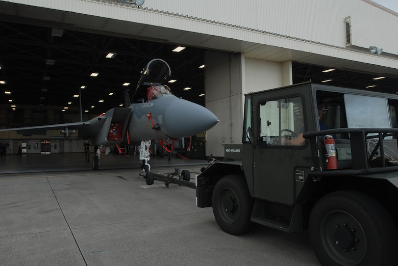 Kadena Airmen tow an F-15C Eagle fighter jet from the flightline into a hangar during preparation for Typhoon Nari on Sept. 14, 2007, at Kadena Air Base, Japan. The base prepared itself for typhoon by moving jets and equipment from the flightline into protective aircraft shelters. The typhoon will hit the island the evening of Sept. 14 with 45 knot winds gusting to 65 knots.  (U.S. Air Force photo/Senior Airman Darnell T. Cannady)