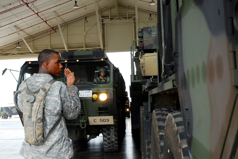 Private 1st Class Aaron Griges guides a truck loaded with Patriot missile equipment from the 1-1 Air Defense Artillery Battalion into a hangar as part of typhoon preparation at Kadena Air Base, Japan, Sept. 14, 2007. Typhoon Nari is the 2nd of the year for Okinawa and is expected to hit the island the evening of Sept. 14 with 45 knot winds gusting to 65 knots.  (U.S. Air Force photo/Airman 1st Class Sheila deVera)
