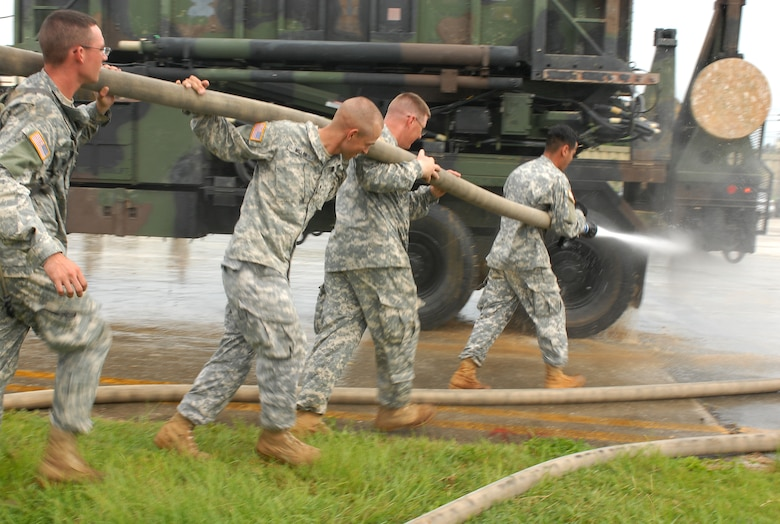 Solders from the 1-1 Air Defense Artillery Battalion hose down all their heavy equipment before they park them into a hanger to weather Typhoon Nari at Kadena Air Base, Japan, Sept. 14, 2007. The typhoon will hit the island the evening of Sept. 14 with 45 knot winds gusting to 65 knots. (U.S. Air Force photo/Airman 1st Class Kelly Timney)