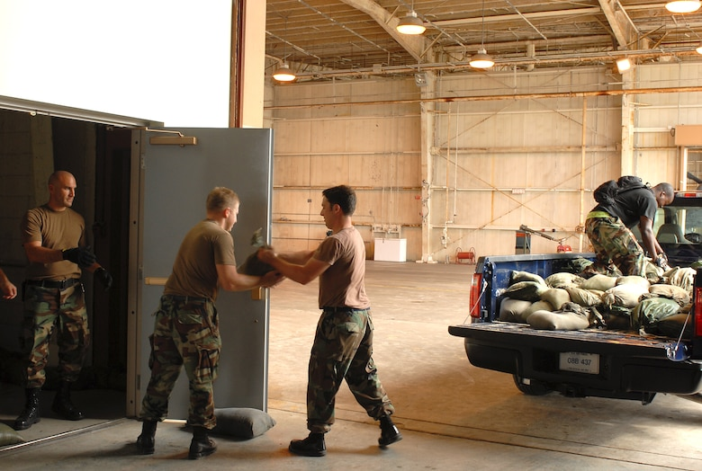 Airmen from the 33rd Rescue Squadron unload sandbags and stack them in front of where their tools are stored to keep water from Typhoon Nari from ruining them at Kadena Air Base, Japan, Sept. 14, 2007. The typhoon will hit the island the evening of Sept. 14 with 45 knot winds gusting to 65 knots. (U.S. Air Force photo/Airman 1st Class Kelly Timney)