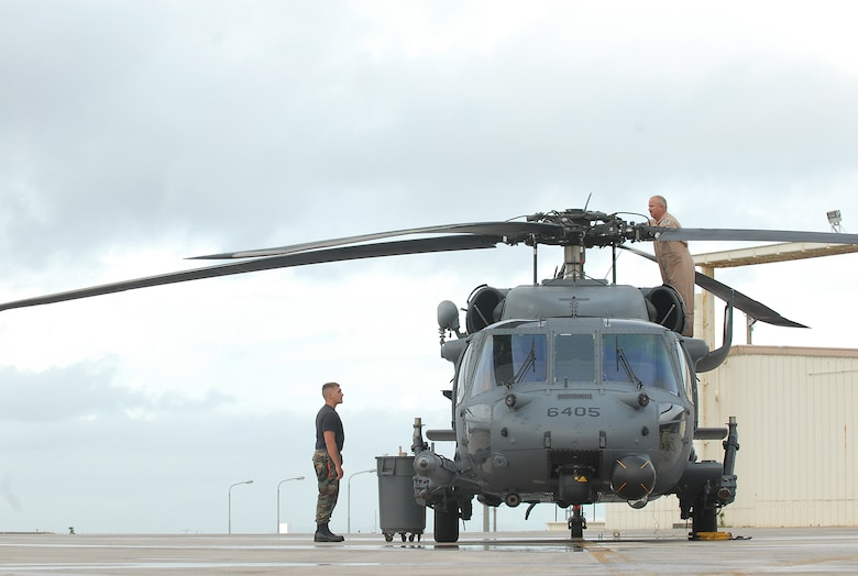 Members from the 33rd Rescue Squadron prep a HH-60 Helicopter for bed down during Typhoon Nari preparation at Kadena Air Base, Japan, Sept. 14, 2007. The base prepared itself for typhoon by moving jets and equipment from the flightline into protective aircraft shelters. The typhoon will hit the island the evening of Sept. 14 with 45 knot winds gusting to 65 knots.  (U.S. Air Force photo/Airman 1st Class Kelly Timney)