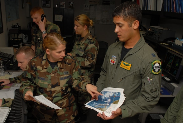 Tech. Sgt. Tonya Trythall shows Capt. Nelson Tirado the storm path of Typhoon Nari path at Kadena Air Base, Japan.  Sept. 14, 2007.  The base prepared itself for typhoon by moving jets and equipment from the flightline into protective aircraft shelters and evacuated many aircraft to locations throughout the Pacific. The typhoon will hit the island the evening of Sept. 14 with 45 knot winds gusting to 65 knots. Sergeant Trythall with the 18th Operations Support Squadron weather flight and Captain Tirado is an aircraft commander with the 82nd Reconnaissance Squadron. (U.S. Air Force Photo/Ms. Junko Kinjo)