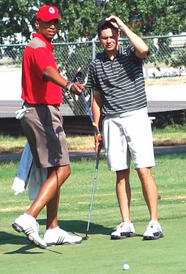 Albert Johnson, left, and Kolby Seals discuss strategy on the green during the Labor Day Golf Tournament at the Tinker Golf Course on Sept. 3. (Air Force photo by John E. Banks)