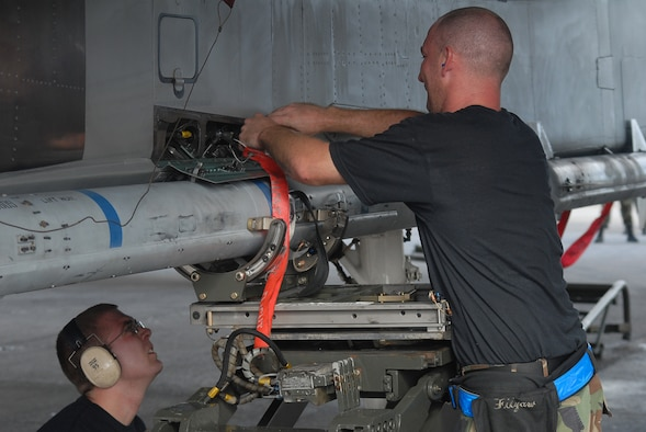 Airman 1st Class Josh Kulaszemicz watches as Staff Sgt. William Filyaw secures a connection on an air-to-air missile on a F-15C during the weapons loading competition at Kadena Air Base, Japan, Sept. 12, 2007. This tests the team's ability of loading F-15s in a fast and safe manner. This competition was held between the 44th and 67th aircraft maintenance units of the 18th Maintenance Squadron. Both Airmen are a weapons load crew members with the 44th AMU. (U.S. Air Force Photo/Senior Airman Darnell T. Cannady)