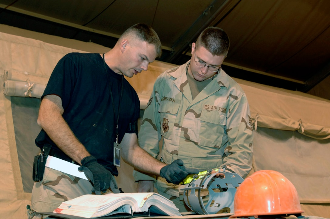 Tech. Sgt. Michael Knight, deployed from Aviano Air Base, Italy, and Staff Sgt. Jesse Gietzen, deployed from Luke Air Force Base, Ariz., review technical orders before assembling a joint direct attack munition Oct. 9, 2005. Both Airmen are assigned to the 332nd Expeditionary Maintenance Squadron at Balad Air Base, Iraq. (U.S. Air Force photo/Staff Sgt. Shannon Kluge)