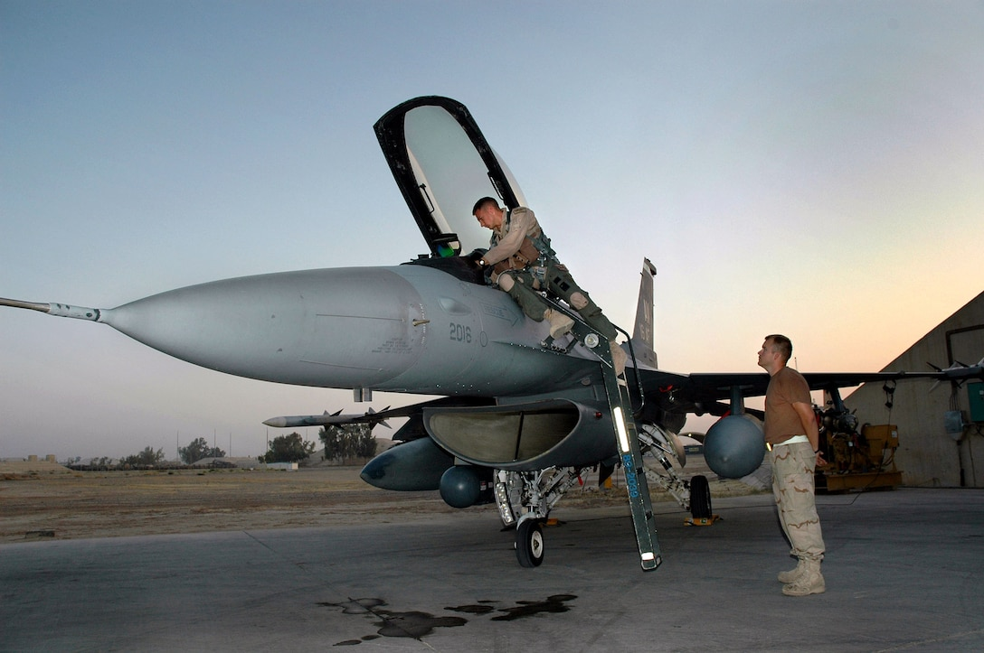 Senior Airman Gaylon Hardman (right), a crew chief with the 332rd Expeditionary Aircraft Maintenance Squadron, waits to assist F- 16 pilot Capt. Bart Wilbanks prepare for a combat mission in support of Operation Iraqi Freedom Sept. 20, 2005. Both Airmen are from the 31st Fighter Wing at Aviano Air Base, Italy, and deployed to Balad Air Base, Iraq.  (U.S. Air Force photo/Maj Robert Couse-Baker)