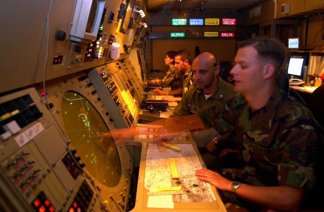 Italian and U.S. Air Force radar controllers, Staff Sgts. Marcello Zappia (left) and Matthew Sandner,  communicate through a vast network of people and equipment within the radar approach control or RAPCON at Aviano Air Base, Italy, in  June 2003. The RAPCON prevents the safe operation of aircraft in the base's air space, coordinates the movements of air traffic and minimizes the delay of aircraft traveling in and out of the airspace. Sergeant Sandner is assigned to the 31st Operations Support Squadron. (U.S. Air Force photo/Airman 1st Class Isaac L. Freeman)