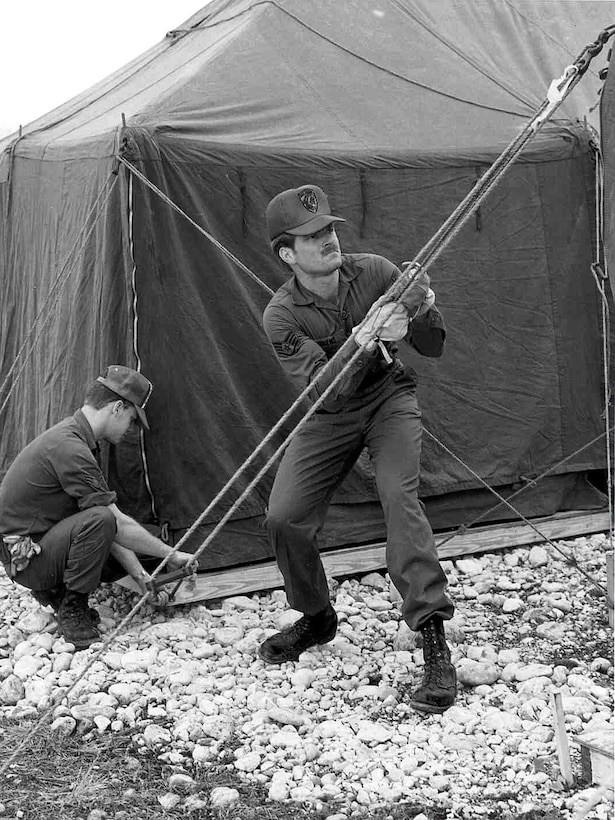 Two RED HORSE members begin setting up tents during 1986, at Aviano Air Base, Italy.  The base needed to set up a tent city for an incoming rotational deployment.  (Courtesy photo)