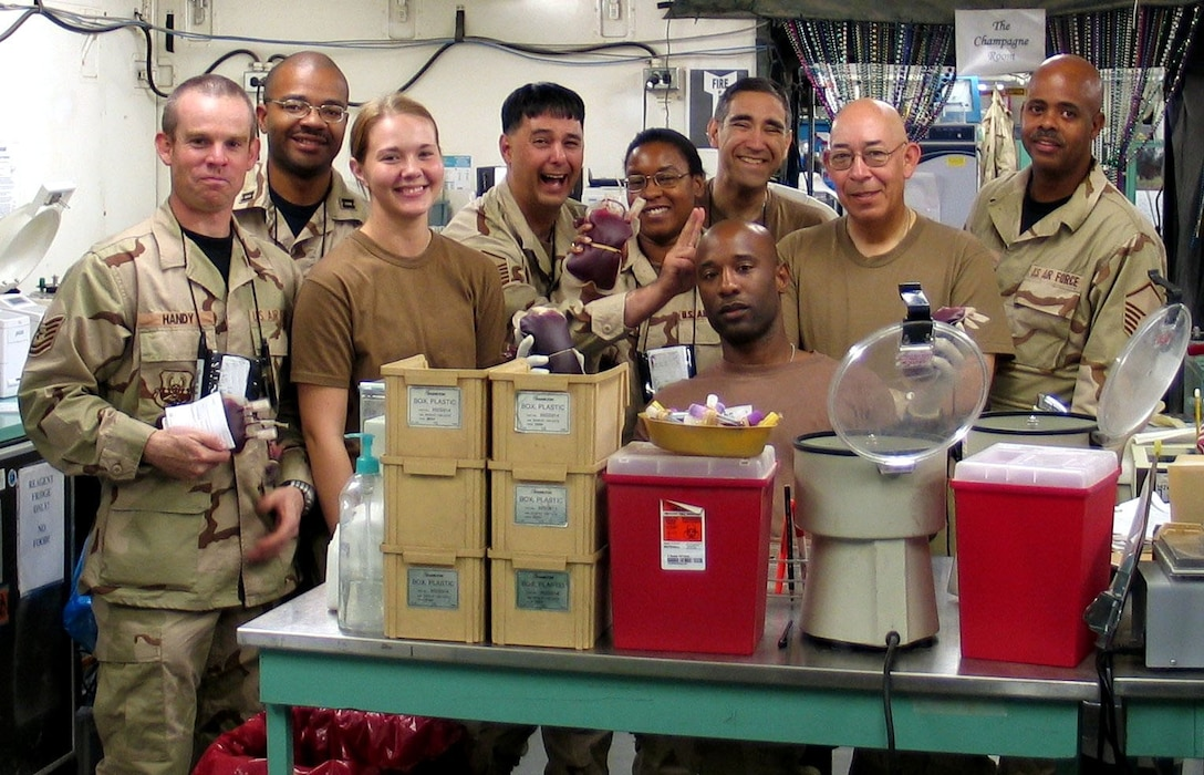 Medics and doctors from the 31st Medical Group deployed to Southwest Asia pause for a group photo after receiving a shipment of blood plasma.  These Airmen were assigned to the 379th Expeditionary Medical Group  in 2005. (Courtesy photo)