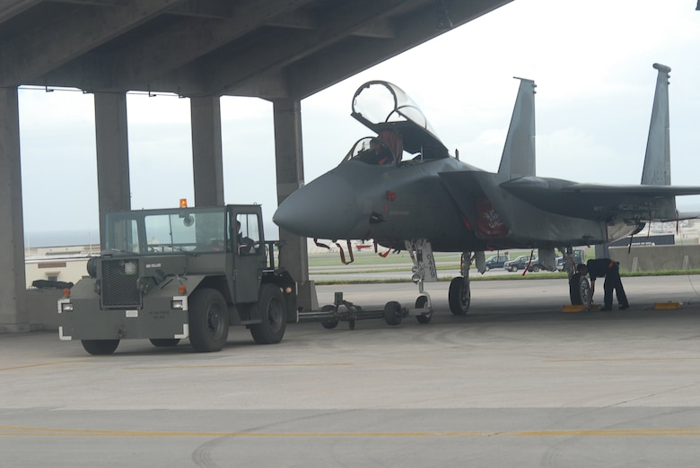 Kadena Airmen tow an F-15C Eagle fighter jet from the flightline into a protective aircraft shelter during preparation for Typhoon Nari on Sept. 14, 2007, at Kadena Air Base, Japan. The base prepared itself for typhoon by moving jets and equipment from the flightline into protective aircraft shelters. The typhoon will hit the island the evening of Sept. 14 with 45 knot winds gusting to 65 knots.  (U.S. Air Force photo/Senior Airman Darnell T. Cannady)