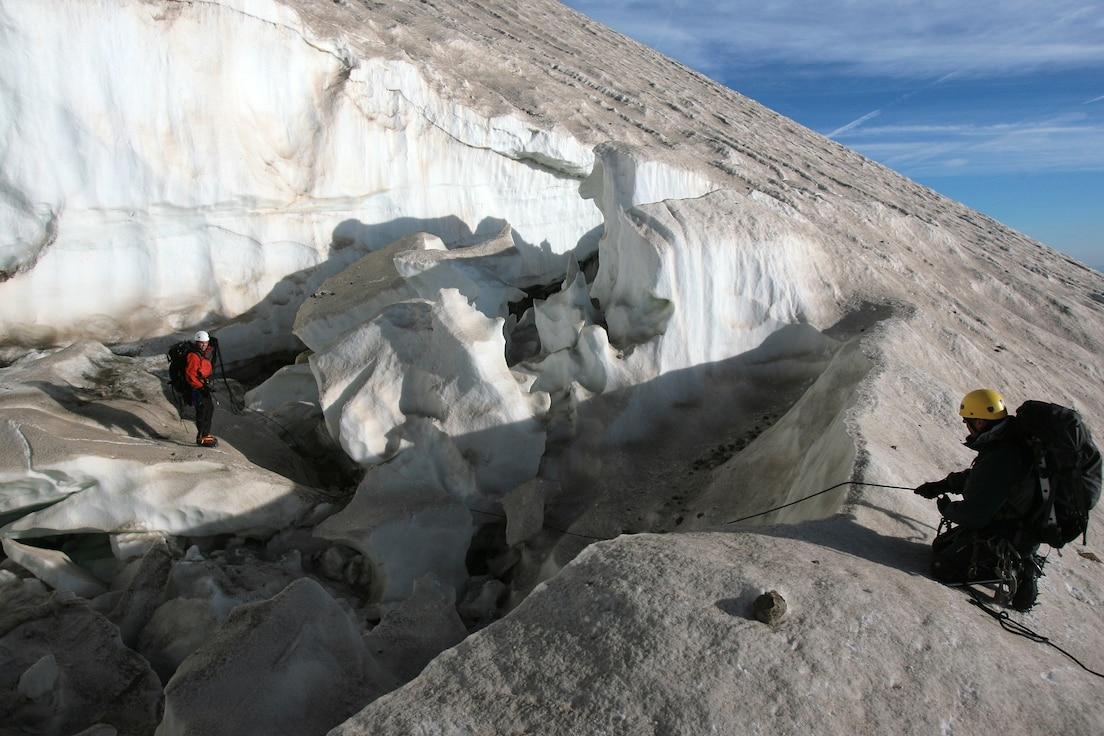Inside a gaping crevasse at 9,500 feet, Tech Sgt. Anthony Reich, pararescueman, 304th Rescue Squadron, Portland, Ore., carefully makes his way around a couple of large ice blocks that have peeled off a melting glacier on Mount Hood, Ore. September 8.  Belaying Sergeant Reich with a safety rope is Staff Sgt. Patrick Dunne, pararescueman, 308th Rescue Squadron, Patrick Air Force Base, Fla.  The two were part of big weekend search for the bodies of two mountain climbers presumed killed during a firece December snowstorm.  An additional four pararescuemen from the 304th RQS and one SERE (search evasion resistance and escape) specialist from the 943rd Rescue Group, Tuscon, Ariz., joined Sergeants Reich and Dunne on the mountain.  In all their were 59 climbers, most of them volunteers from civilian moutain groups searching the high country.