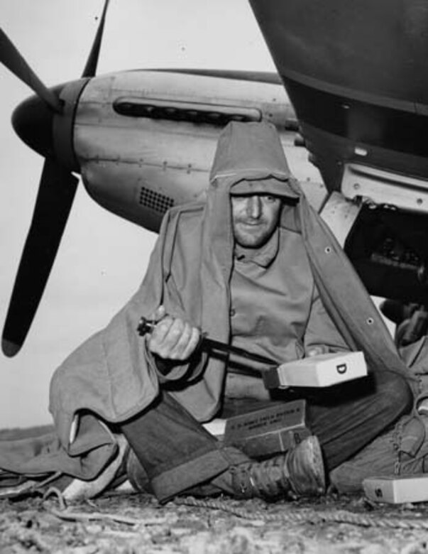 Huddled under a canopy blanket beneath the Wing of his 7th Air Force P-51 fighter on Iwo Jima, Crew Chief SSgt. Anthony A. Belesi, cuts open dry K-rations. Mechanics remained on the flight line 14 hours from dawn to dark with no shelter. (USAF file photo)