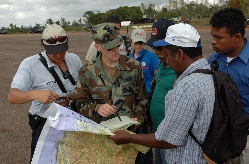PUERTO CABEZAS, Nicaragua - Locals and U.S. State Department Office of Foreign Disaster Assistance help Air Force Maj. Jason Clark find coordinates for small communities on a map Sept. 16.  Aircrews and UH-60s from Joint Task Force Bravo in Honduras deployed here to distribute U.S. relief materials.  The U.S. State Department and Department of Defense are working together to bring food, water and other needed items to small communities on the Nicaraguan coast that were affected by the hurricane.  (Army photo by Specialist Grant Vaught)