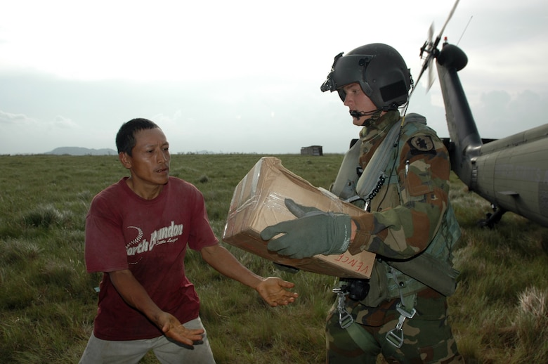 PUERTO CABEZAS, Nicaragua – Spc. Lucas Gomez hands a box of food to a local man here Sept. 15.  Specialist Gomez is part of the 1-228th Aviation Battalion deployed to Nicaragua from Soto Cano Air Base in Honduras, to provide relief after Hurricane Felix.  The U.S. State Department and Department of Defense are working together to bring food, water and other needed items to small communities on the Nicaraguan coast that were affected by the hurricane.  (Army photo by Specialist Grant Vaught)