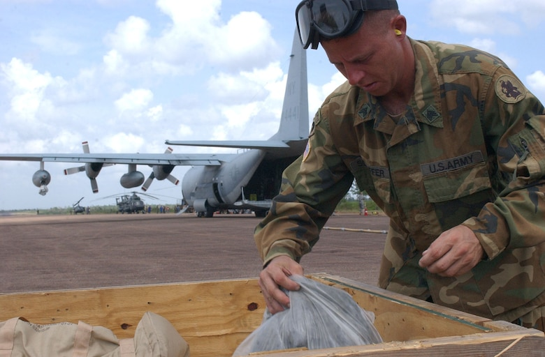 PUERTO CABEZAS, Nicaragua – Army Sgt. Robert Schaffer, 1st Battalion, 228th Aviation Regiment at Soto Cano Air Base, Honduras, retrieves supplies from a bin near a U.S. Marine Corps KC-130 assigned to the Marine Aerial Refueler Transport Squadron 452 (VMGR-452) here Sept. 15.  Sergeant Schaffer assisted with the setup of an Advanced Aviation Forward Area Refueling System to refuel aircraft supporting relief missions following Hurricane Felix. (U.S. Air Force photo by Tech. Sgt. Sonny Cohrs)