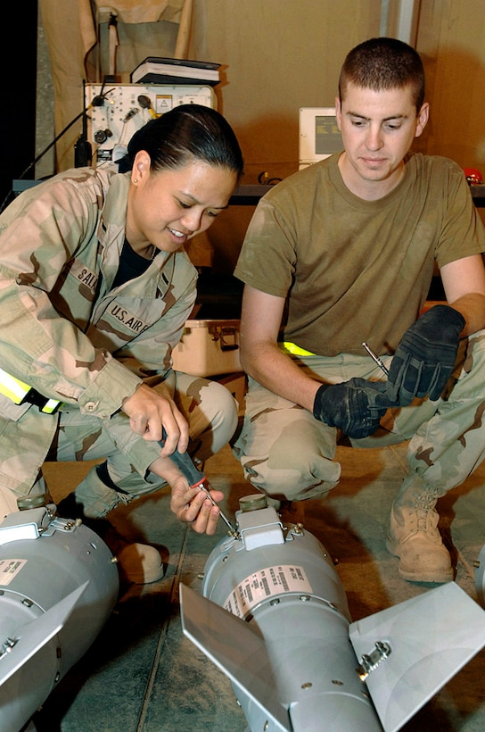 1st Lt. Roseline Salazar and Staff Sgt. Philip Krug work on a tail fin assembly before assembling a joint direct attack munition at Balad Air Base, Iraq, Oct. 9, 2005. Both Airmen are assigned to the 322nd Expeditionary Maintenance Squadron and deployed from Aviano Air Base, Italy. (U.S.  Air Force photo/Staff Sgt. Shannon Kluge)