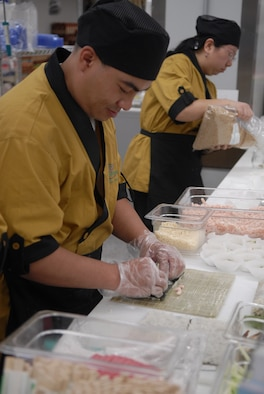 Employees at Andersen's newly opened sushi bar inside the commissary prepare sushi during the grand opening Sept. 13. In the first two days of the sushi bar being open, it generated more sales than any commissary stateside did in a two-day period. (Photo by Airman 1st Class Daniel Owen)