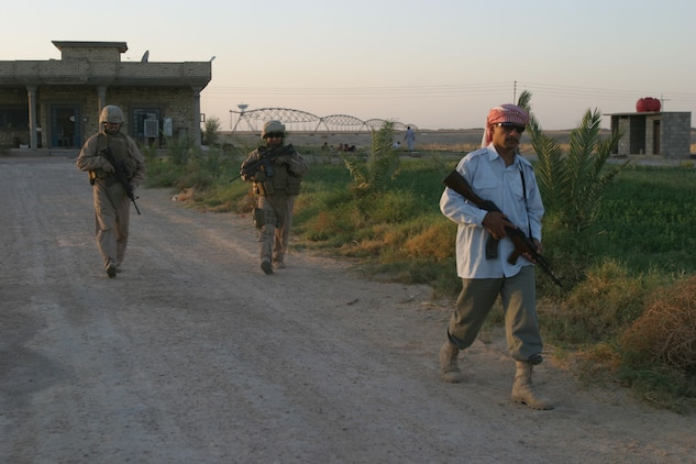 Corporals Alan J. Bennett (left) and Luis A. Valadez with 3rd Platoon, Battery C, 1st Battalion, 12th Marine Regiment (1/12), Task Force Military Police (TFMP) and an Iraqi Highway Policeman patrol near the Traffic Control Point on ASR Golden on 18 September 2007. The patrol was conducted to build community relations and gain intelligence on local insurgents. 1/12, TFMP is deployed with Multi National Forces-West in support of Operation Iraqi Freedom in the Al Anbar province of Iraq to develop Iraqi Security Forces, facilitate the development of official rule of law through democratic reforms, and continue the development of a market based economy centered on Iraqi reconstruction. (Official USMC photograph by Cpl. Thomas Lew)