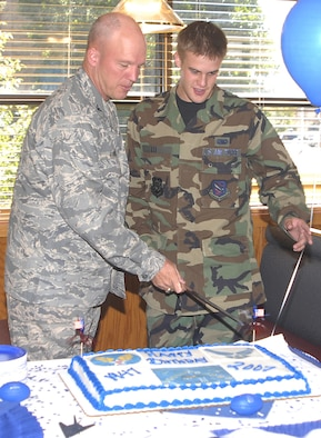 Col. Jay Raymond, 21st Space Wing commander, and Airman Michael Lee, 21st Logistics Readiness Squadron, cut the Air Force's ceremonial birthday cake Sept. 18 at the Aragon Dining Facility. The Air Force marks its 60th birthday this year. (U.S. Air Force photo)