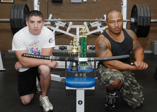 Airman 1st Class Brandon Reyes (left), 27th Medical Group, and Tech. Sgt. Kevin Parker, 27th Fighter Wing information manager, display the trophies they won at the New Mexico Region Power Lifting meet in Albuquerque on Sept. 8. Airman Reyes competed in the Novice Class and Parker competed in the 220-pound Sub Masters II division. (U.S. Air Force photo by Airman 1st Class Eric Cardenas)