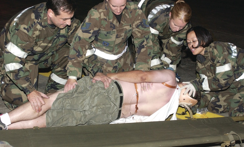"""A triage team (first responders) rolls their """"wounded victim"""" onto a gurney before taking him to the casualty collection point. (U.S. Air Force photo by Amy Abbott)"""
