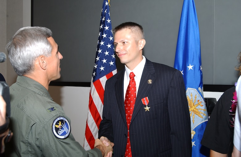 Col. J.J. Torres, 15th Airlift Wing commander, thanks Special Agent Gregory Carmack for his service, after the Bronze Star presentation ceremony.