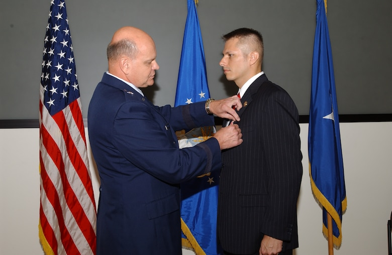 Brig. Gen. Dana Simmons, Air Force Office of Special Investigations commander, presents the  Bronze star with Valor to Special Agent  Gregory A. Carmack for his heroism.