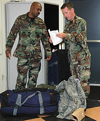 Reservists Staff Sgt. Demond Loggins, left, and Master Sgt. Chris Webster, 446th Civil Engineer Squadron, review their departure checklist Sept. 10 as they prepare to head out to Wisconsin, and then Iraq.  Fourteen Airmen from the 446th Airlift Wing will be joining forces with the 819th RED HORSE Squadron, Malmstrom AFB, Mont., for a six-month deployment. (U.S. Air Force photo/Sandra Pishner)