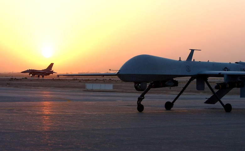 An MQ-1 Predator unmanned aerial vehicle and F-16 Fighting Falcon return from an Operation Iraqi Freedom combat mission. Both aircraft provide intelligence, search and reconnaissance gathering features, as well as munitions capability to support ground troops and base defense. (U.S. Air Force photo/1st Lt. Shannon Collins)