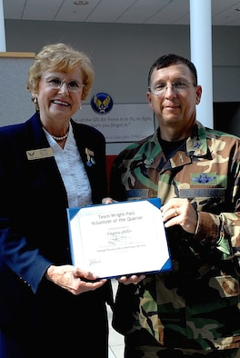 DAYTON, Ohio -- Virginia Miller (left), a volunteer at the National Museum of the United States Air Force, accepts the Team Wright-Patt Volunteer of the Quarter award from 88th Air Base Wing Vice Commander Col. James H. Strickler. (U.S. Air Force photo)